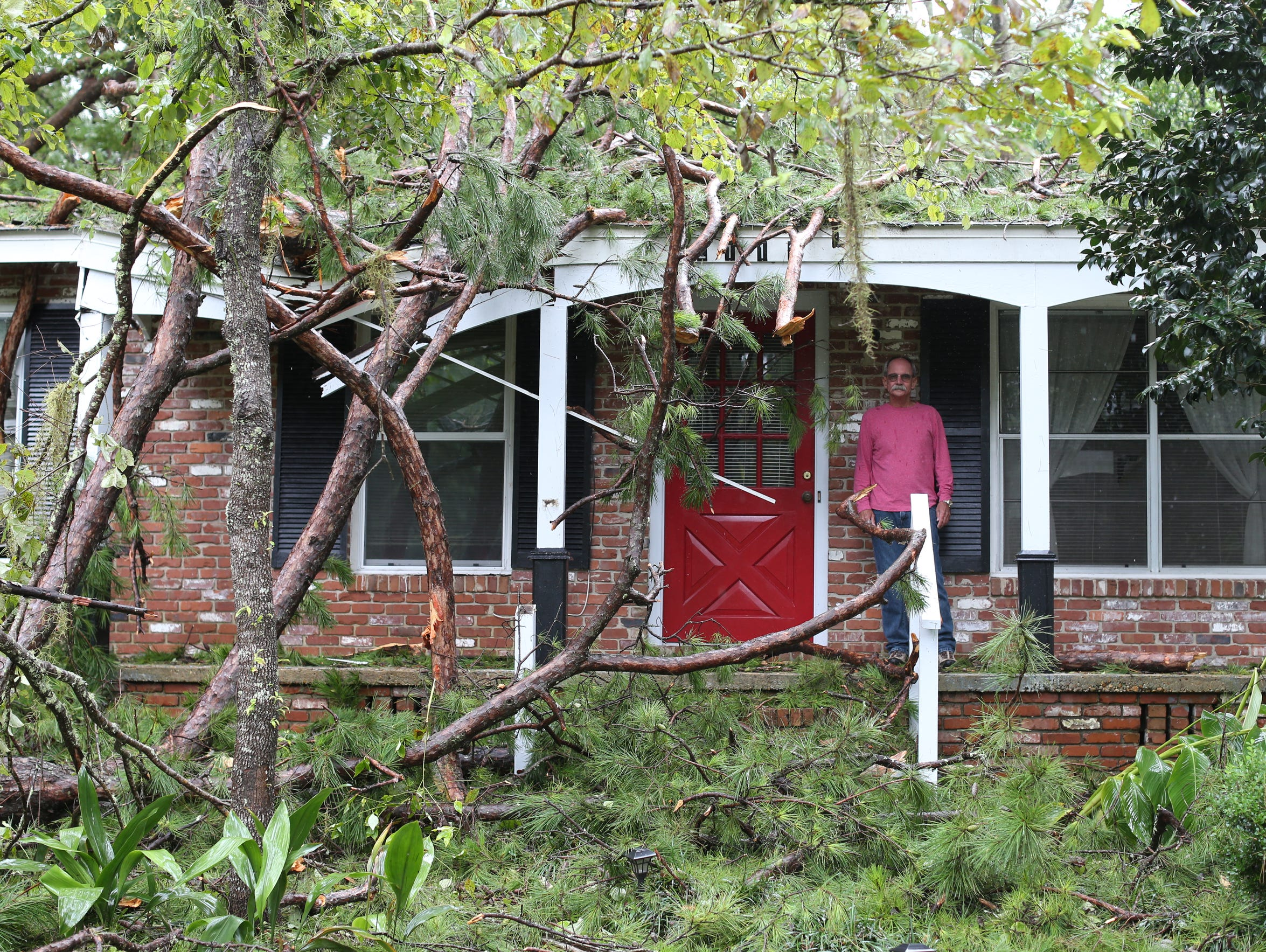 Steve Donelan stands on the porch of his Mahan Road home Sep 11 after Irma brought a pine tree crashing into his roof.