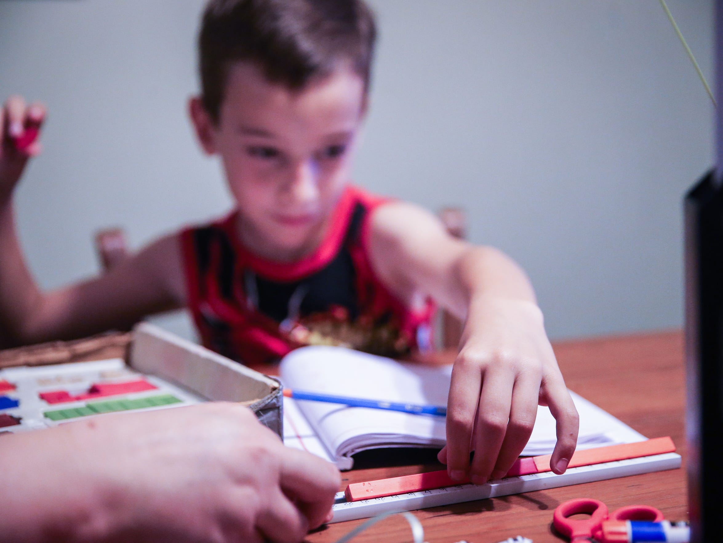 Egan, 6, adds math rods to complete an equation at