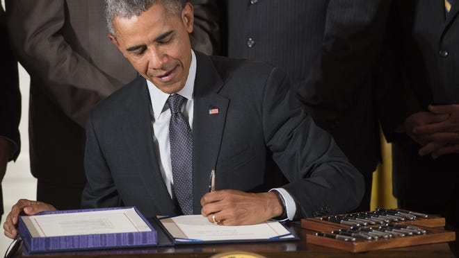 US President Barack Obama signs H.R. 1295 Trade Preferences Extension Act of 2015, which includes assistance for Americans who lost their jobs to foreign outsourcing, during a bill signing ceremony in the East Room of the White House in Washington, D.C., June 29, 2015. Obama also signed H.R. 2146 Defending Public Safety Employees' Retirement Act, which includes fast track trade promotion authority  that allows Obama to negotiate trade treaties, including the Trans Pacific Partnership.