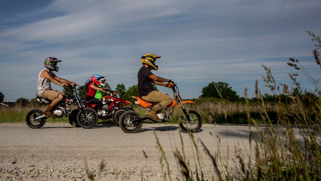 People ride dirt bikes past the Casco Township Hall Thursday, June 8, 2017 in Casco Township.