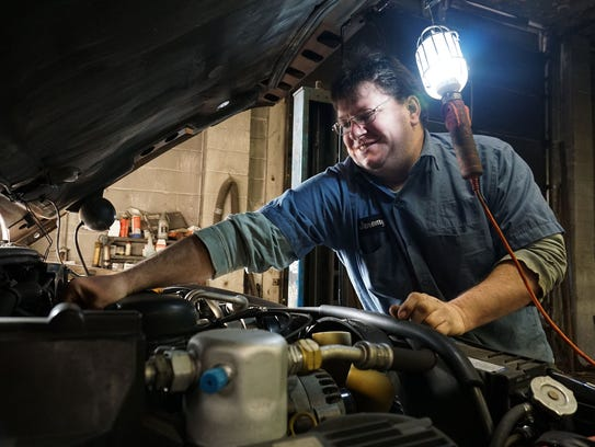 Jeremy Aumend works on an SUV at his business, Jeremy's
