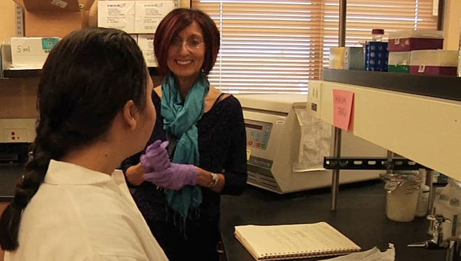 NMSU Regents Professor Elba Serrano is shown discussing an experiment with a student in her lab.