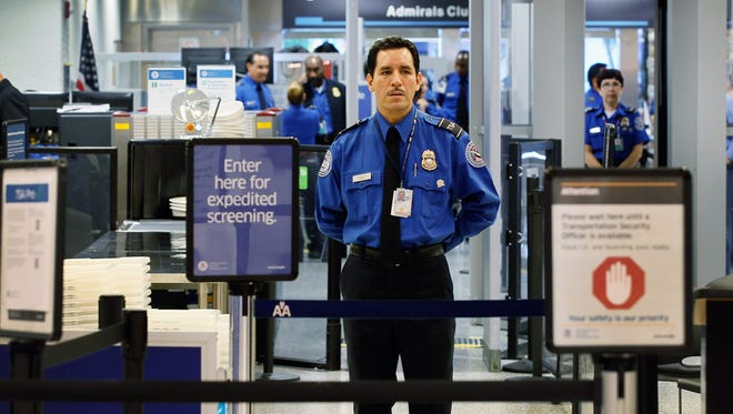 A Transportation Security Administration agent waits to screen passengers at Miami International Airport on October 4, 2011.