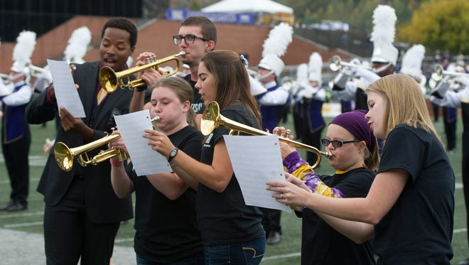 With a little help from their peer mentors, students from WCU's University Participant Program perform with the Pride of the Mountains Marching Band during the Homecoming football game last fall.