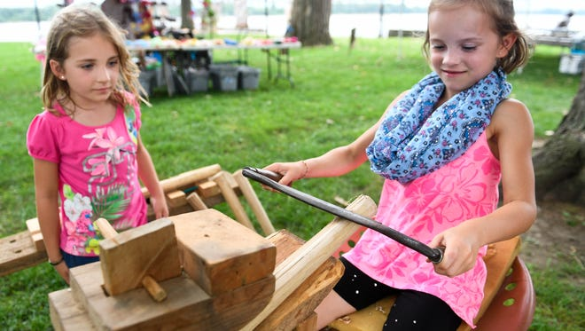 Sydney Cunningham (left), 5 years-old, watches her sister Bella Cunningham, 7, use a draw knife to taper a chair leg at Peter Chevalier's woodworking demonstration at the Henderson Bluegrass in the Park Folklife Festival last year.