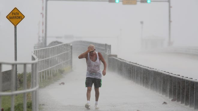 Steve Pearson, of Clearwater, is pummeled by a squall of rain during a walk on the Dunedin Causeway as thunderstorms moved through Pinellas County bringing wind and heavy rain, Monday, Aug. 29, 2016, in Dunedin, Fla. Authorities at some locations in the Tampa-St. Petersburg area of Florida are hauling out sandbags to offer residents amid predictions of heavy rains from a storm system heading to the southeast Gulf of Mexico. (Douglas R. Clifford/Tampa Bay Times via AP)