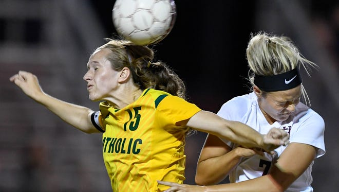 Catholic's Ambere Barnett (15) and Henderson's Carlee Crafton (7) battle for control of the ball as the Lady Colonels play Owensboro Catholic in the last game of the regular season at Colonel field Thursday, October 5, 2017.