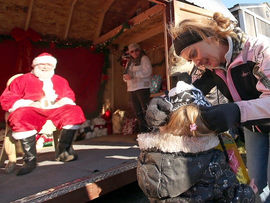 Elizabeth Carr puts a new winter hat on a youngster after they visited with Santa and received a gift outside of her Camp Union Saloon.