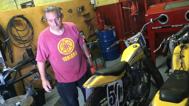 Even though he is hampered by a knee injury, Steve Kasten moves his racing motorcycles around his shop in Hatley on Monday, Aug. 31, 2015