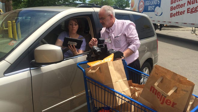 Amy Steffens, of Whitmore Lake, takes advantage of  the Brighton Meijer's new curbside pickup service. Meijer corporate representative Kevin Shafer assisted her with the order Wednesday.