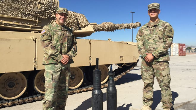 Lt. Col. Alexis Rivera Espada, left, stands with his Abrams tank in the background and his gunner, Sgt. Jonathan Luna from Pittsburg, Calif.