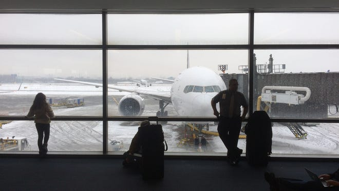 Travelers look out at winter weather conditions from inside Terminal C Saturday morning at Newark Airport in Newark, NJ on December 17, 2016.