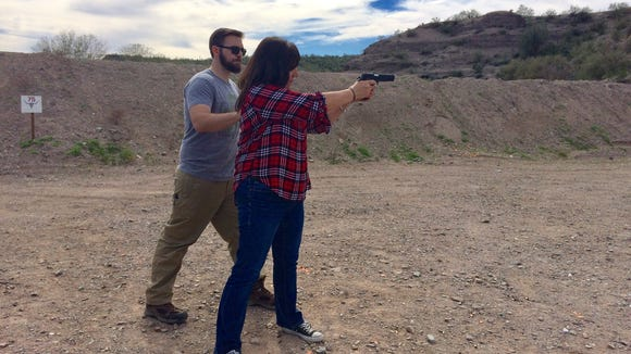 Virgil Bland instructs Karina Bland in firing a pistol at Cowtown, a shooting range and training facility.