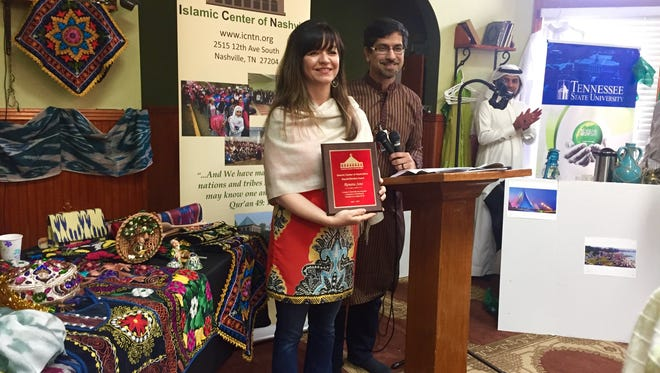 Rashed Fakhruddin, right, honors Renata Soto with the Beyond Borders Award at the Islamic Center of Nashville's Diversity Brunch on April 1, 2017, for her work toward a more inclusive Nashville.