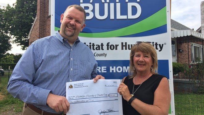 Executive Director of Habitat for Humanity of Franklin County, Thomas Reardon, receives a $300 donation from Baxter Group, Inc. owner and CEO, Jocelyne Melton on June 20.