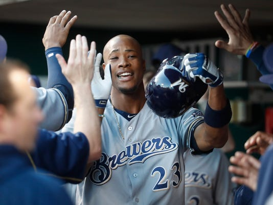 Milwaukee Brewers' Keon Broxton (23) celebrates in the dugout after hitting a solo home run off Cincinnati Reds starting pitcher Dan Straily during the second inning of a baseball game, Tuesday, Sept. 13, 2016, in Cincinnati. (AP Photo/John Minchillo)