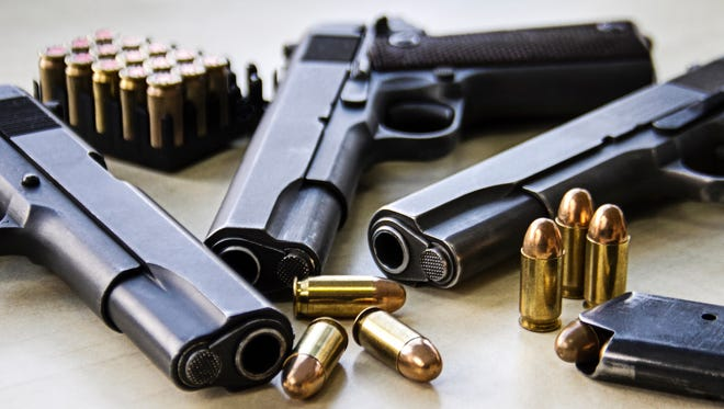 Three pistols lie  on a table with bullets.
