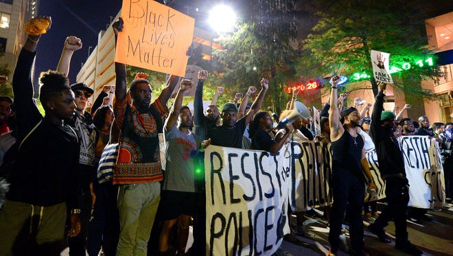 Protesters stand in unity in Charlotte on Friday as they prepare to march throughout the city to protest Tuesday's fatal police shooting of Keith Lamont Scott.