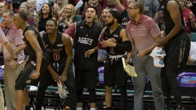The New Mexico State bench cheers late in the second half of the team's NCAA college basketball game against Miami at the Diamond Head Classic tournament, Saturday, Dec. 23, 2017, in Honolulu. New Mexico State won 63-54.