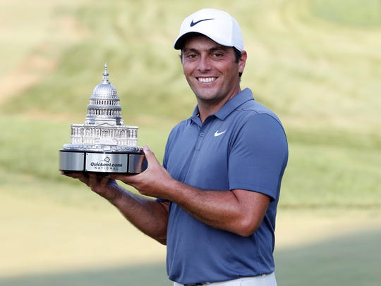 Francesco Molinari of Italy celebrates with the championship trophy after winning the Quicken Loans National golf tournament at TPC Potomac at Avenel Farm on July 1, 2018, in Potomac, Maryland.