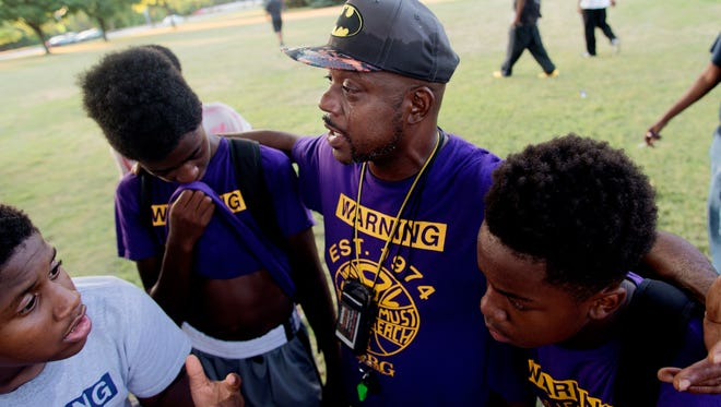 Coach Eric Moore, teary eyed, comforts his team after their playoff loss at Meaux Park in Milwaukee.
