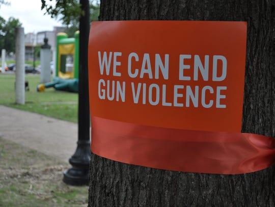 A sign attached to a tree at Saturday's Wear Orange