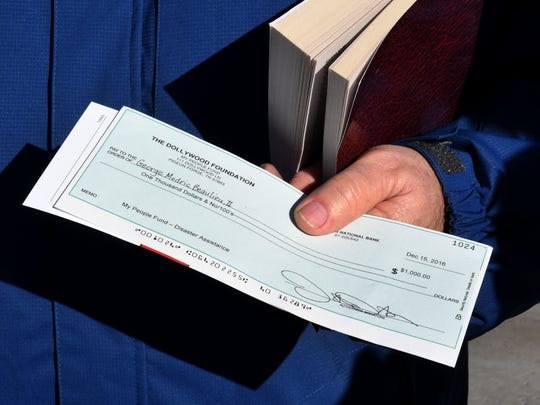 George Beaulieu holds his $1,000 check from the Dollywood Foundation's My People Fund which was  distributed Thursday, Dec. 15, 2016 at the LeConte Center in Pigeon Forge.