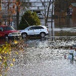In this Friday, Dec. 25, 2015 photo, flood waters from the Chattahoochee River covers streets in Columbia, Ala. An Alabama official said volunteers have worked to distribute sandbags as flooding remained a major concern after severe storms battered the state. (Jay Hare/Dothan Eagle via AP) MANDATORY CREDIT