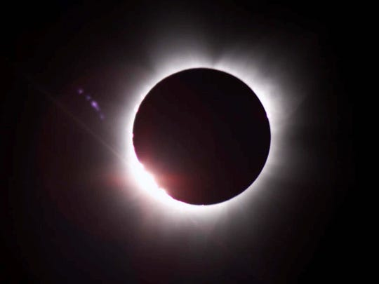 The sun's corona peeks out from behind the moon during
