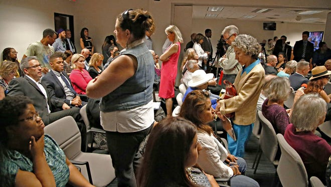 Disgruntled members of the public turn their back on Arizona Secretary of State Michele Reagan as she addresses the state House Elections Committee hearing on March 28, 2016.