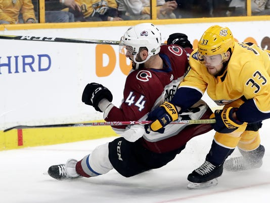 Colorado Avalanche defenseman Mark Barberio (44) and Nashville Predators left wing Viktor Arvidsson (33), of Sweden, chase the puck during the second period in Game 1 of an NHL hockey first-round playoff series Thursday, April 12, 2018, in Nashville, Tenn. (AP Photo/Mark Humphrey)