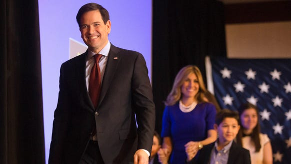 Marco Rubio walks on the stage with his family in Des