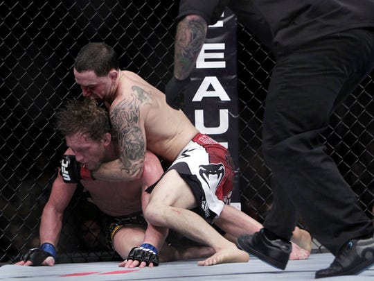 Frankie Edgar finishes off Gray Maynard during their lightweight title bout at UFC 136 in Houston.