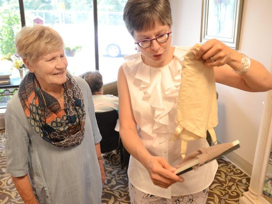 Barbara Armstrong of Milford looks at a garter girdle, found by Karen Schaefer, right, as part of a weddings-past collection on display at Milford's West Hickory Haven Nursing Home.