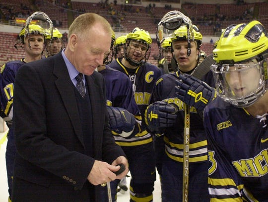 Red Berenson shows his game puck to his players after