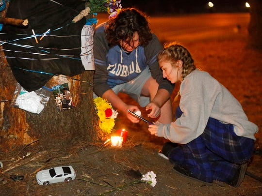 Siegel High School juniors Jacob Jones, left and Cerrandon Omilian, right light candles on Monday, Dec. 4, 201, under the tree were fellow Siegel junior Will Divilbiss was killed late Saturday night, Dec. 4, 2017, in a wreck.