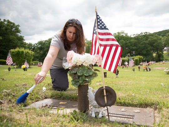 Krista Vest cleans dirt off the grave of her grandparents'