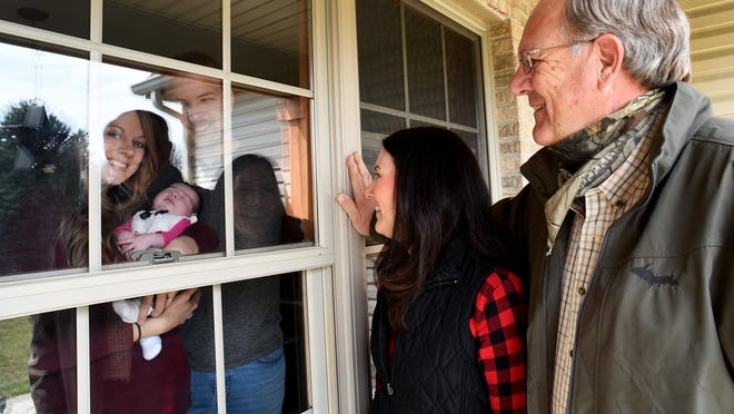 Brian and Rachel Pearch of Petersburg hold their newborn baby girl, Klara, born April 13, as grandparents, David and Janet Wehner of Ida, take a closer look through the window due to COVID-19 restrictions.