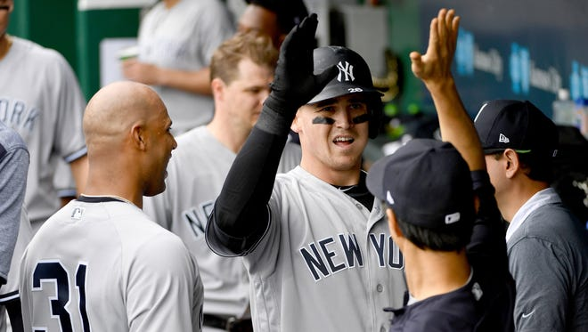 New York Yankees first baseman Tyler Austin (26) is congratulated in the dugout after scoring in the fifth inning.