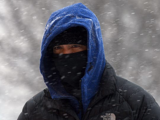 A man is bundled up against the snow and wind as he