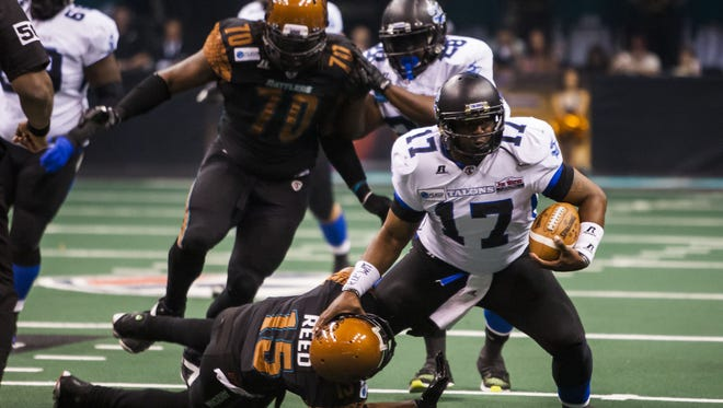 Rattlers' Kerry Reed (15) tackles Talons quarterback Shane Boyd (17) during the Arizona Rattlers and San Antonio Talons arena football game at US Airways on Saturday, April 26, 2014 in Phoenix.