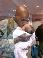 In this photo provided by Dinetta Scott, James Brown holds his month-old daughter Jayliah right before Brown was returning to Iraq in 2010 for deployment.