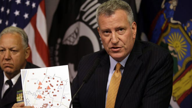 New York City Mayor Bill de Blasio holds a map showing the location in the Bronx borough of cooling towers, red triangles, and people, red dots, that were infected with Legionnaires' disease during a news conference to provide an update of the Legionnaires' disease outbreak.