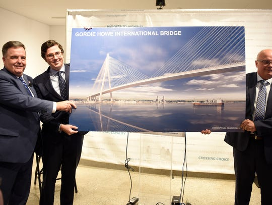 Dwight Duncan, left, Alfonso Sanchez, center and Tom Middlebrook, hold a rendering of the new Gordie Howe bridge.