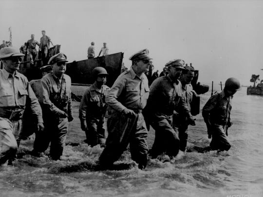 Gen. Douglas MacArthur wades ashore at Palo Beach during initial landings at Leyte, Philippine Islands.