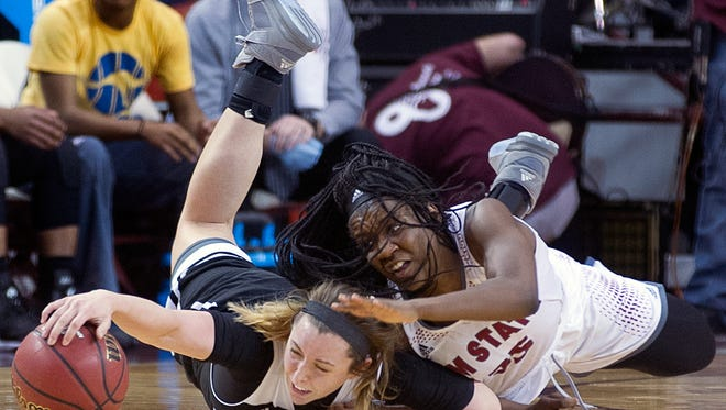 New Mexico State's Moriah Mack fights for a loose ball with UMKC's Justice Collins Saturday afternoon at the Pan American Center.