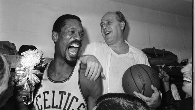 Bill Russell (left) holds a corsage sent to the dressing room as he celebrates with former Boston Celtics coach Red Auerbach after defeating the Los Angeles Lakers to win their eighth straight NBA Championship, in Boston, on April 29, 1966.