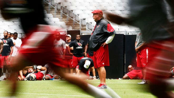 Cardinals head coach Bruce Arians watches his players run during conditioning drills at training camp Friday, July 25, 2014 at University of Phoenix Stadium in Glendale.
