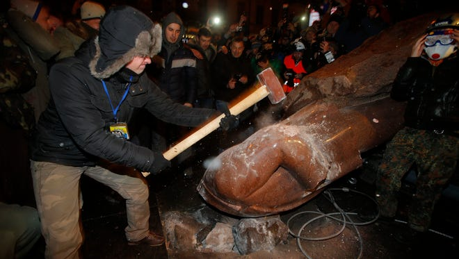 An anti-government protester smashes the statue of Vladimir Lenin with a sledgehammer in Kiev, Ukraine, on Sunday.