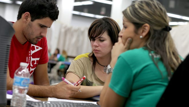 Jose Villanueva, left, and Doraisy Avila sit with Maria Gabriela, an agent from Sunshine Life and Health Advisors, as they price health insurance plans in Miami.